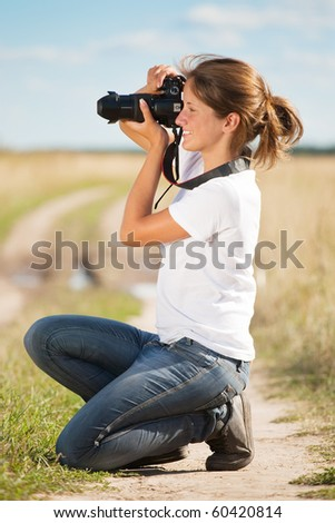Young girl taking photo with camera against field - stock photo