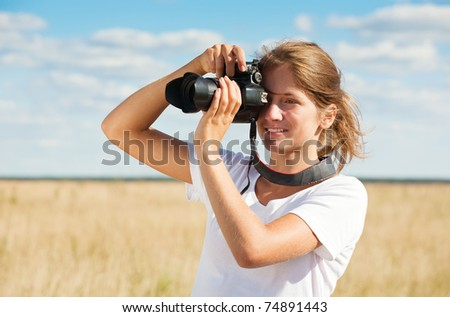Young girl taking photo with camera against field