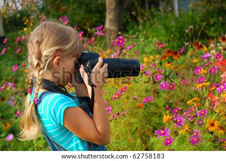 young girl taking photos by professional digital camera in autumn garden