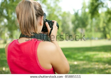 young girl taking picture on natural - stock photo