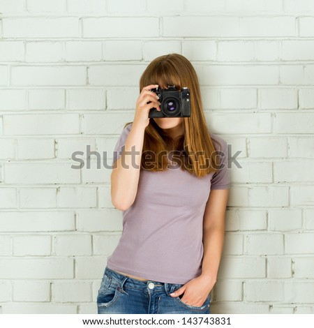 Young girl taking picture with a old vintage camera - stock photo