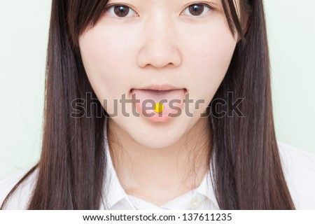 young girl taking pill against pale green background - stock photo