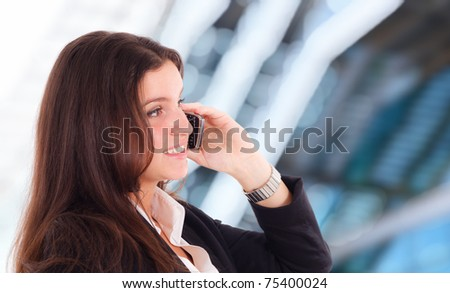 Young girl talking at the cellphone. Blurred blue background. - stock photo
