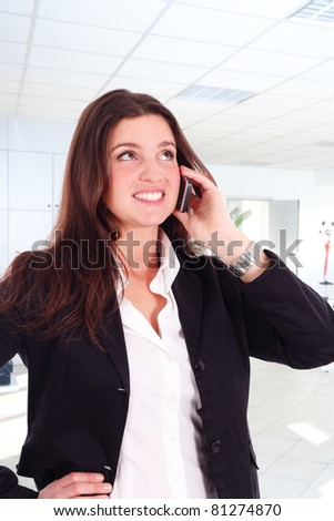 Young girl talking at the cellphone. Office background. - stock photo