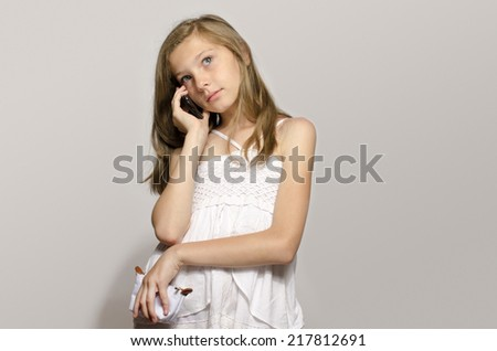 Young girl talking on the phone, teenager using a cellphone and having fun - stock photo