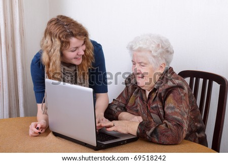 Young girl teaching senior woman to work at computer - stock photo