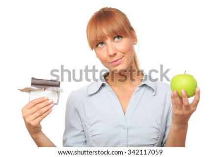 Young girl tempted to eat a chocolate instead of an apple. Isolated on white - stock photo