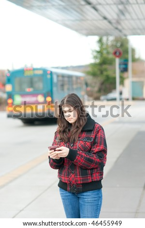 Young girl texting on bus stop. Shallow depth of field. - stock photo