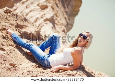 young girl the blonde in jeans, against sand - stock photo