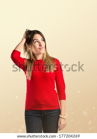 Young girl thinking over ocher background
