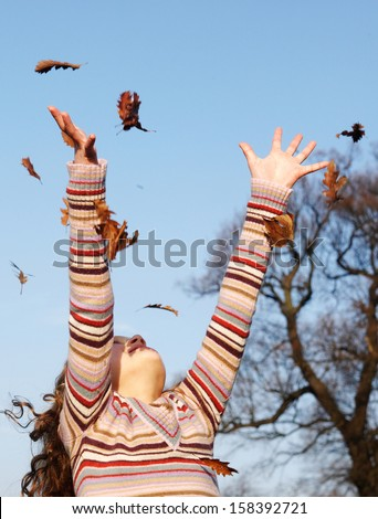 Young girl throwing dry autumn leaves up into the blue sky with her arms and and with floating leaves falling against a bright blue sky and leafless fall trees, outdoors. - stock photo