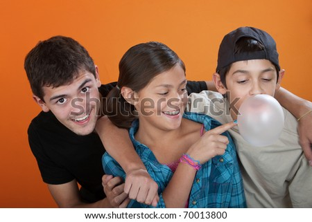 Young girl touching bubble from her brothers chewing gum on orange background - stock photo