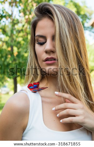 Young girl touching butterfly on her shoulder - stock photo
