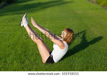 Young girl training at the park. Abdominal prelum exercise. - stock photo