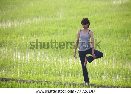 young girl training yoga on sunny paddy field - stock photo