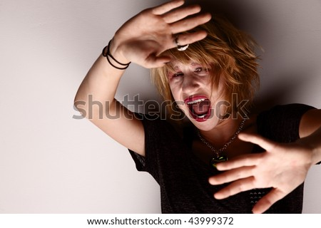 Young girl trapped against a wall and screaming