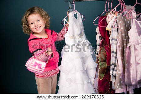 Young girl trying on a white dress - stock photo