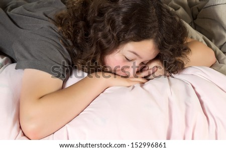 Young girl trying to wake up in the morning with her chin resting on the back of her hands while lying in a messy bed   - stock photo