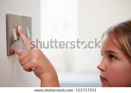 Young Girl Turning Off Light Switch - stock photo