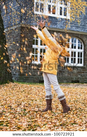 Young girl under falling autumn leaves - stock photo