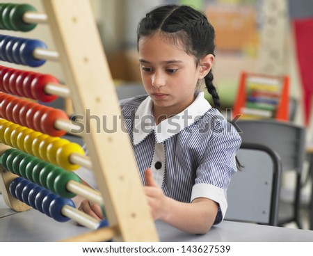 Young girl using abacus in classroom