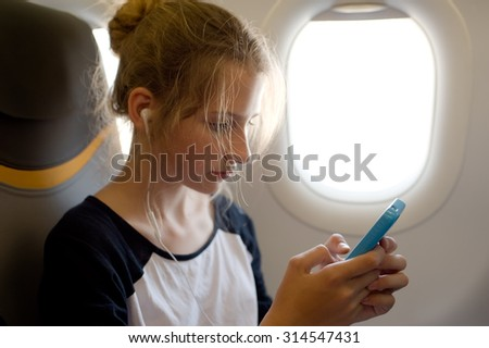 Young girl using cell phone in the airplane
