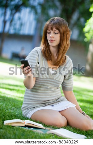 Young girl using cell phone while doing assignment on campus lawn - stock photo