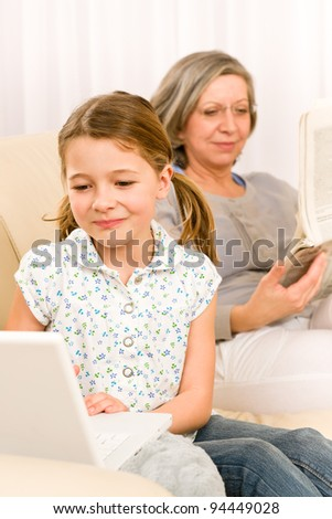 Young girl using computer laptop while grandmother read book at home - stock photo