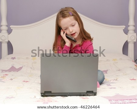 Young girl using laptop and Cell phone - stock photo