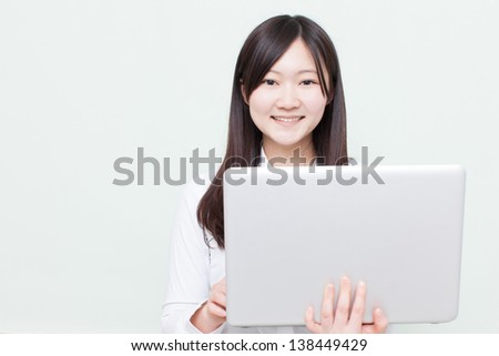 young girl using laptop computer against pale green background - stock photo