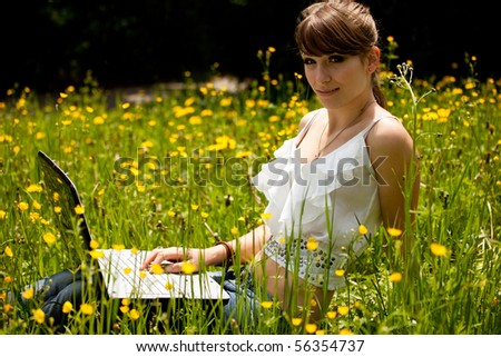 Young girl using laptop outside during a summer day in the park. - stock photo