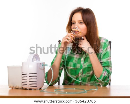 Young girl using nebulizer mask for respiratory inhaler Asthma Treatment isolated on a white background. Close up view. - stock photo
