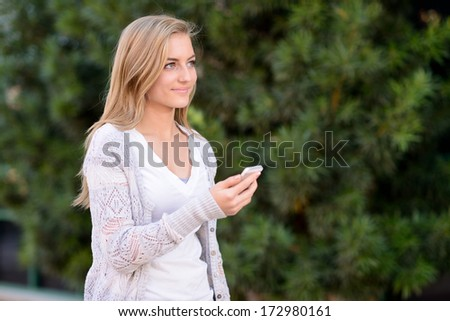 Young girl using smartphone. Teen using a cellphone outside in front of a green tree. - stock photo