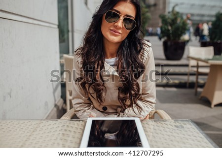 Young girl using tablet pc while sitting outside the cafe. Urban background