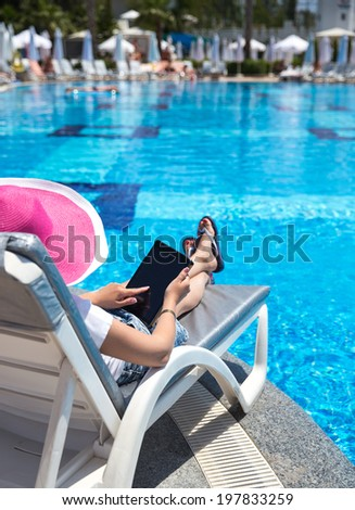 Young girl using tablet while sunbathing near pool