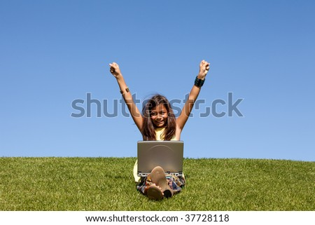 Young girl using wireless internet at the park