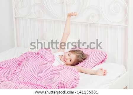 young girl wakes up in the morning in the bedroom - stock photo