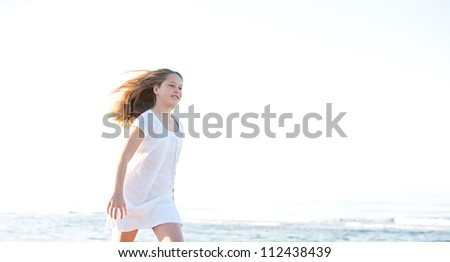 Young girl walking along the shore on a sunny beach with the horizon in the background, smiling and with her hair floating in the breeze. - stock photo