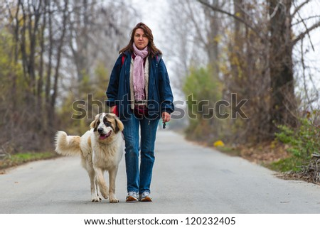 Young girl walking and training her Bucovina shepherd dog on a rural empty road - stock photo