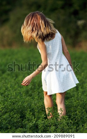 Young girl walking in a clover field - stock photo