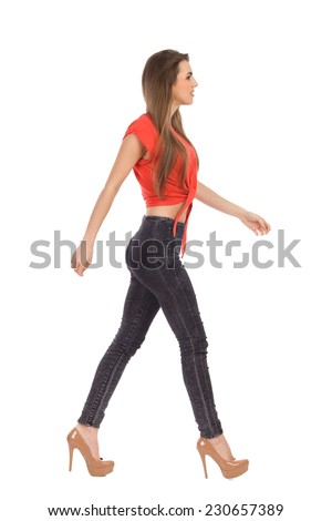 Young girl walking in red top, black jeans and high heels. Side view. Full length studio shot isolated on white. - stock photo