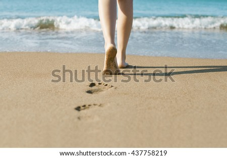 Young girl walking on sandy beach leaving footprints in the sand - stock photo