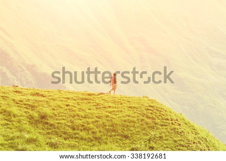 Young girl walking on the top up against the mountain  - stock photo