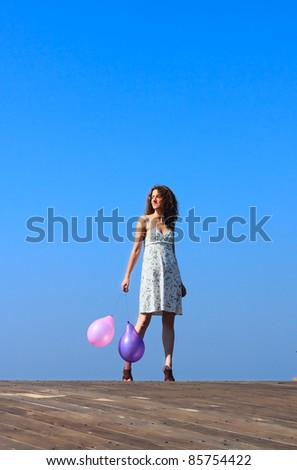 young girl walks and waves the balloons