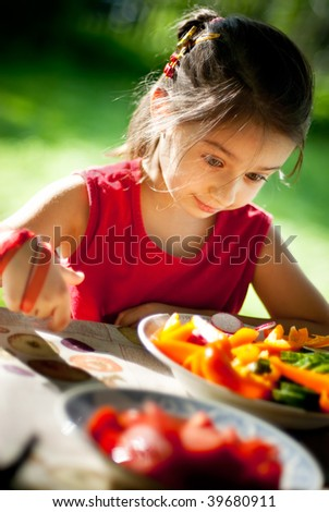 Young girl was delighted, that to it have given plate of cut vegetables - stock photo
