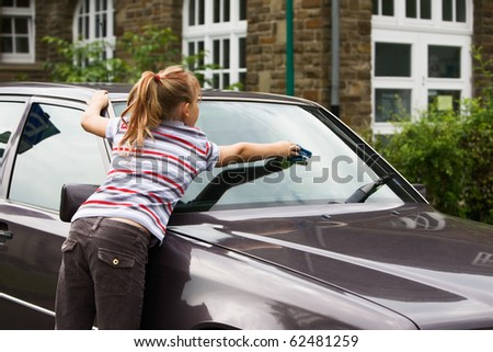 Young girl washing windshield in parking lot, rear view - stock photo