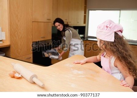 Young girl watching her mother putting cookies into the oven