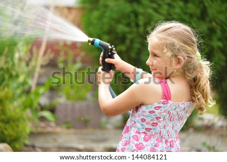 Young girl watering plants in the garden. - stock photo