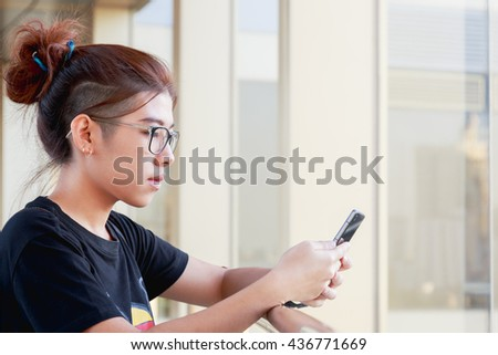 Young girl wear eyeglasses happy with using smartphones to chat with friends, parents and online social/ lifestyle people