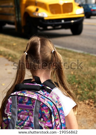 young girl wearing a backpack and waiting for school bus - stock photo